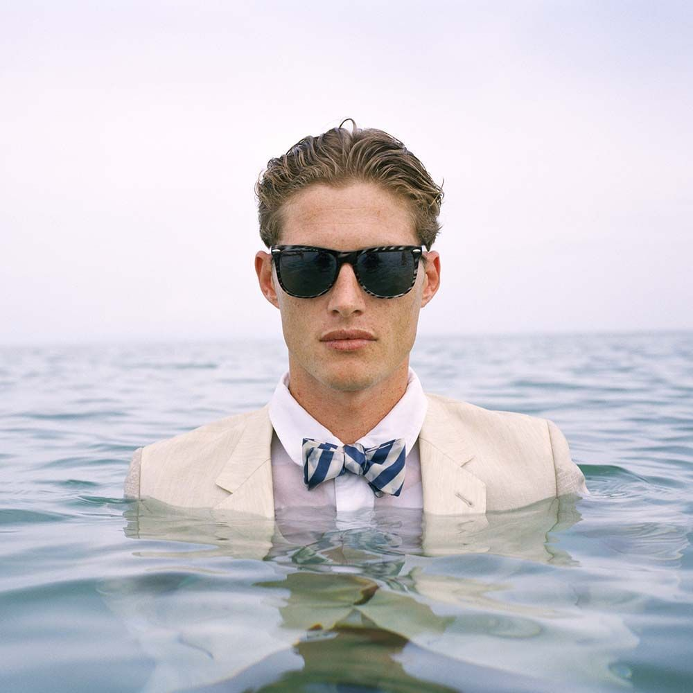 "<span class=""caption-title"">Jimmy Standing in Ocean Wearing Sun Glasses</span>,  Dominican Republic, 2010<span class=""caption-copyright"">© Rodney Smith</span>"