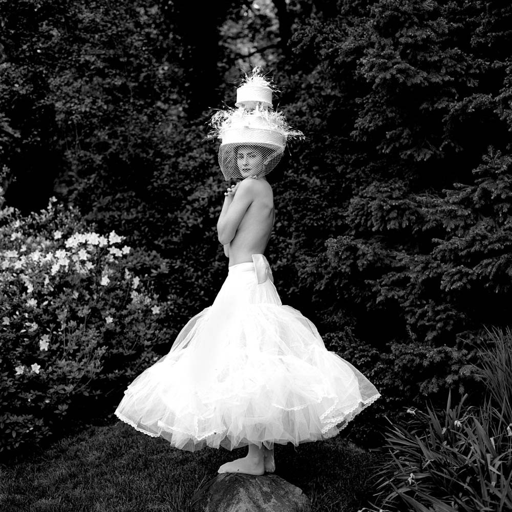 "<span class=""caption-title"">Zoe Wearing Cake Hat while Standing on Rock</span>, Snedens Landing, New York,  2003<span class=""caption-copyright"">© Rodney Smith</span>"