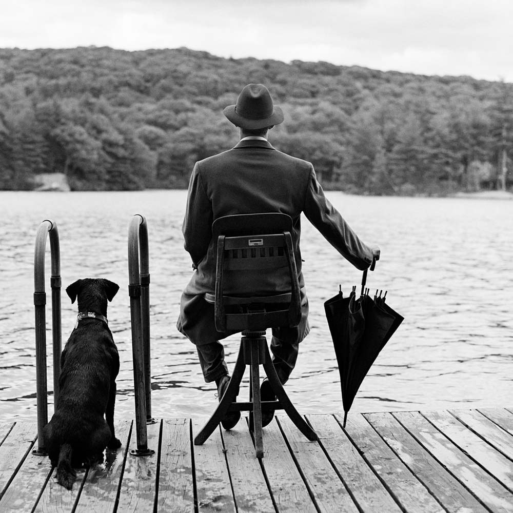 "<span class=""caption-title"">Avril Fisk Seated on Dock with Dog</span>, Harriman, New York, 1994<span class=""caption-copyright"">© Rodney Smith</span>"