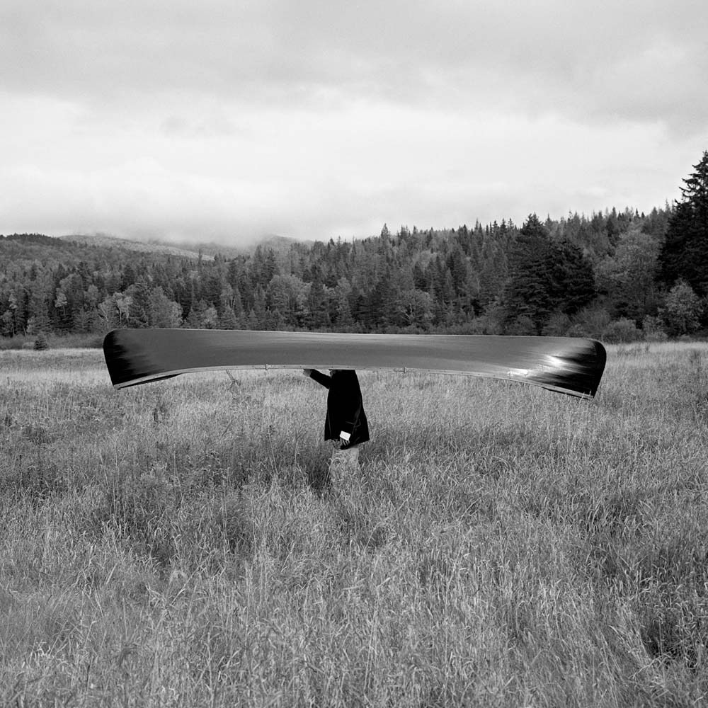 "<span class=""caption-title"">Man with Canoe on Head</span>, Saranac, New York, 1994<span class=""caption-copyright"">© Rodney Smith</span>"