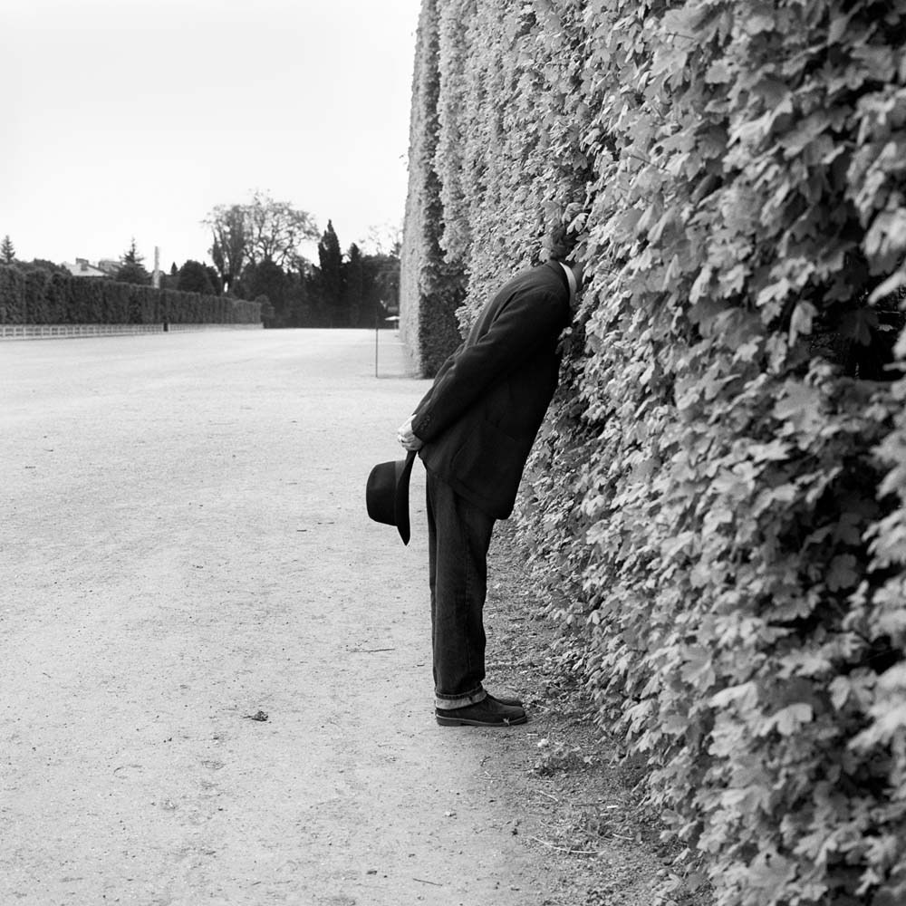 "<span class=""caption-title"">Jonah with Head in Hedge No. 1</span>, Vienna, Austria, 1998<span class=""caption-copyright"">© Rodney Smith</span>"