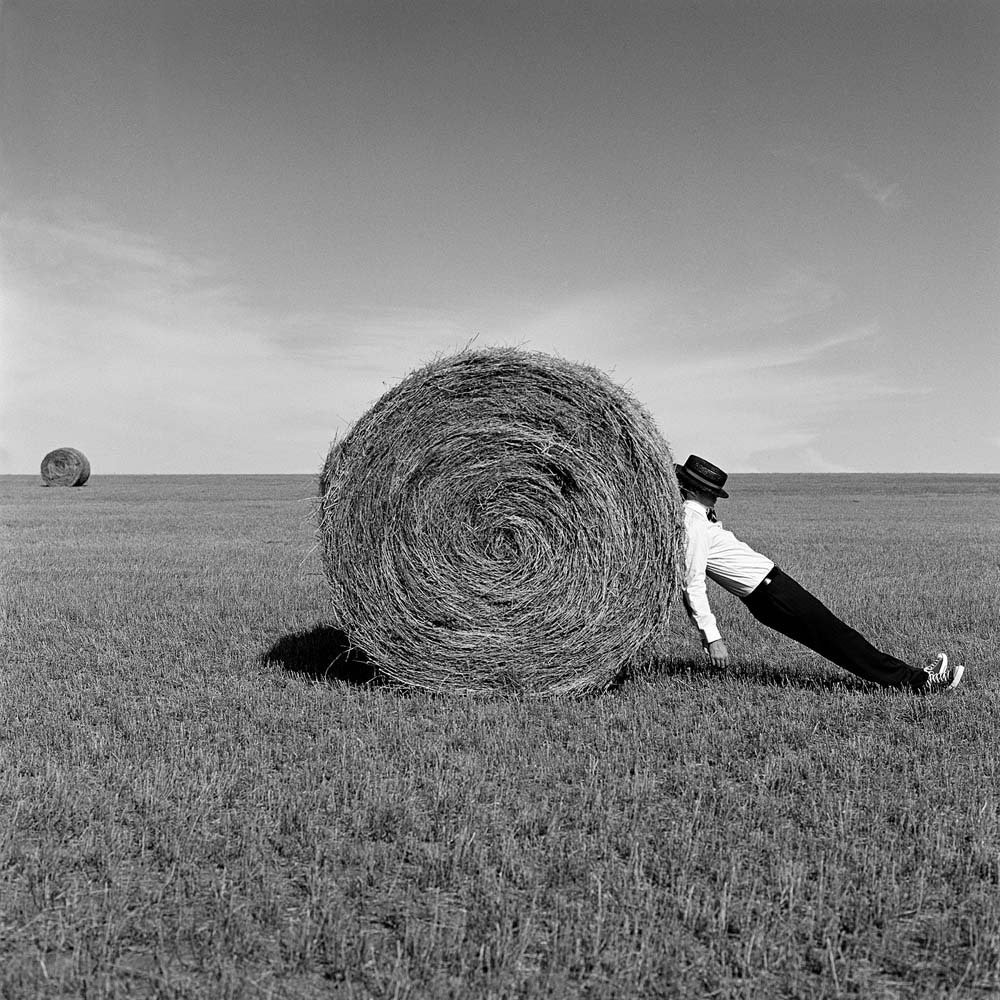 "<span class=""caption-title"">Man Leaning Against Hay Bale</span>, Alberta, Canada, 2004<span class=""caption-copyright"">© Rodney Smith</span>"