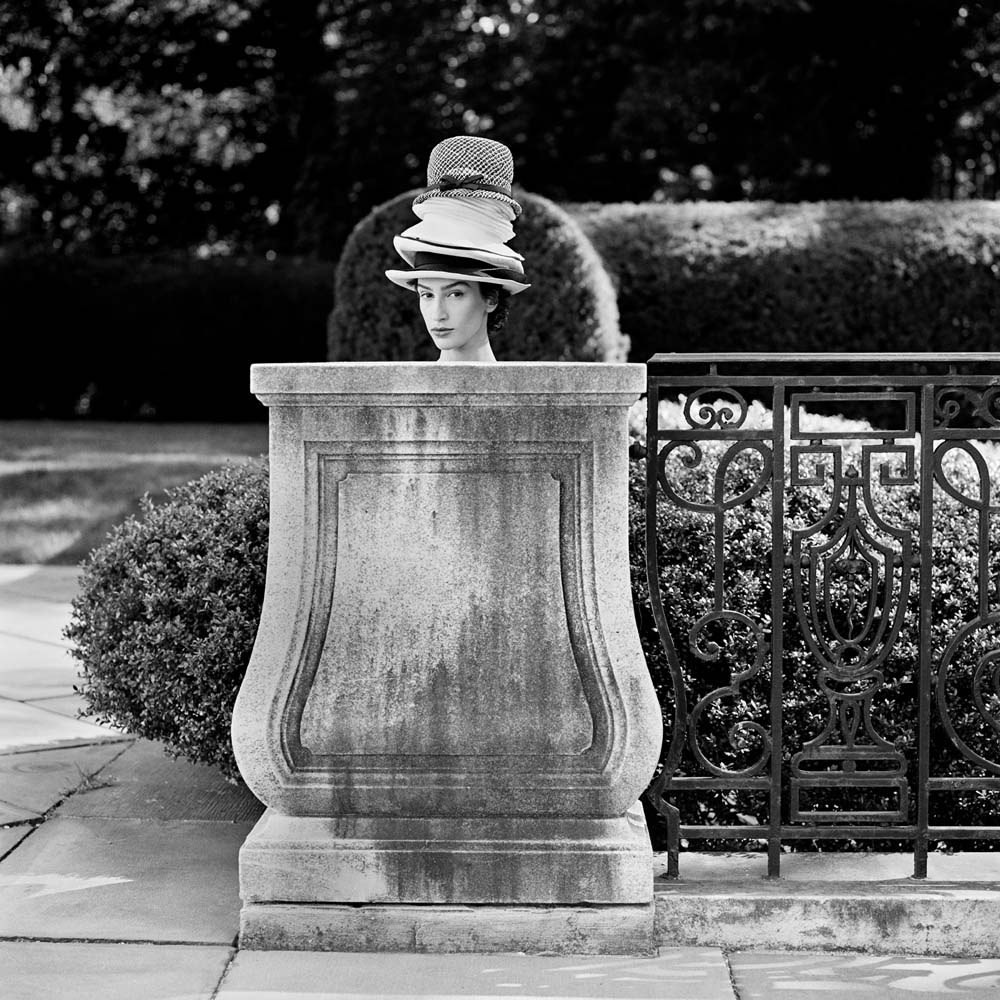 "<span class=""caption-title"">Maria Behind Pedestal with Hats</span>, Long Island, New York, 1993<span class=""caption-copyright"">© Rodney Smith</span>"